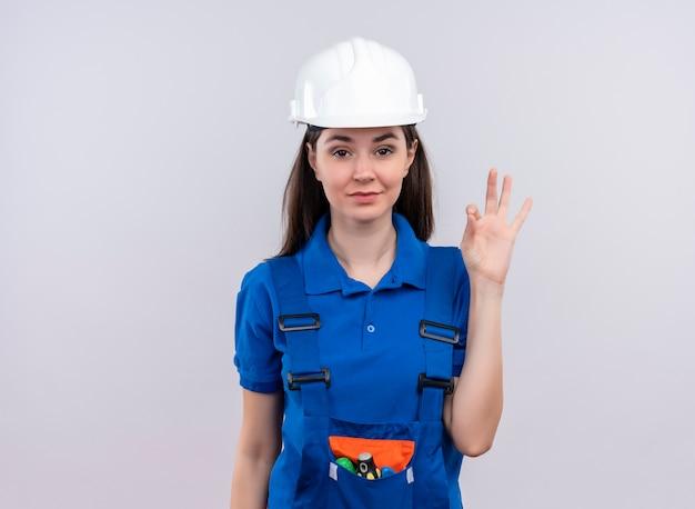 Pewna siebie młoda budowniczy dziewczyna w białym hełmie ochronnym i niebieskim mundurze gesty ok na odosobnionym białym tle z miejsca na kopię