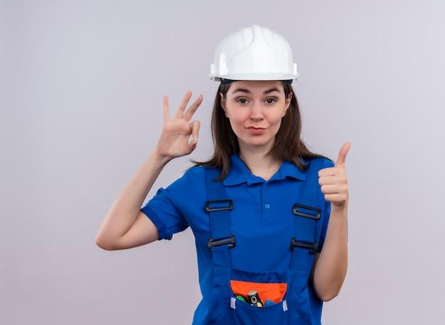 Pewna siebie młoda budowniczy dziewczyna z białym hełmem ochronnym i niebieskim mundurem gestykuluje ok i uderza w górę na odosobnionym białym tle z miejsca na kopię