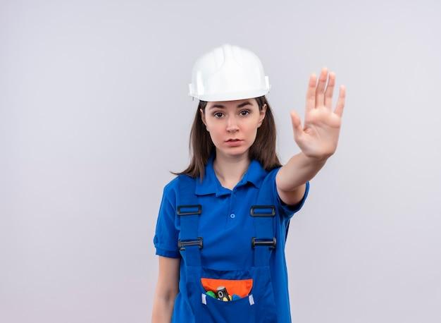 Pewna siebie młoda budowniczy dziewczyna z białym hełmem ochronnym i niebieskimi mundurowymi gestami zatrzymuje się na odosobnionym białym tle z miejscem na kopię