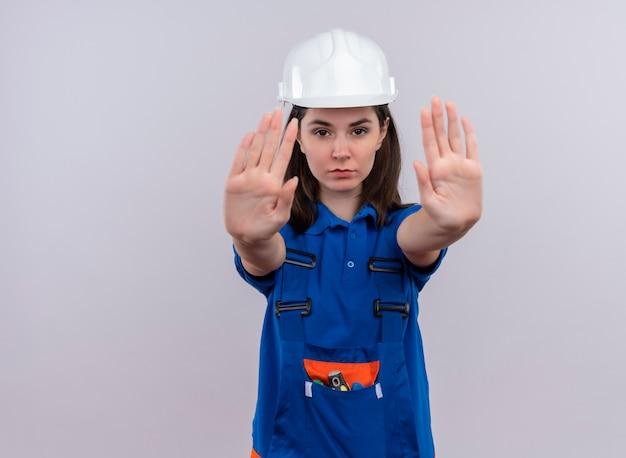 Pewna siebie młoda budowniczy dziewczyna z białym hełmem ochronnym i niebieskimi mundurowymi gestami zatrzymuje się obiema rękami na odosobnionym białym tle z miejscem na kopię