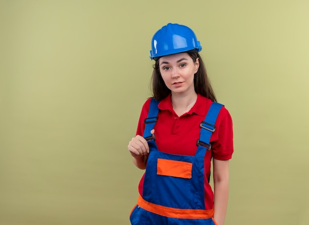Pewna siebie młoda budowniczy dziewczyna z niebieskim hełmem ochronnym trzyma mundur na odosobnionym zielonym tle z miejsca na kopię
