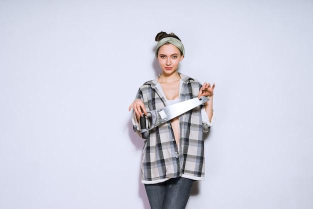 Pewna siebie młoda dziewczyna w koszuli w kratę trzymająca ostrą piłę, naprawa w mieszkaniu