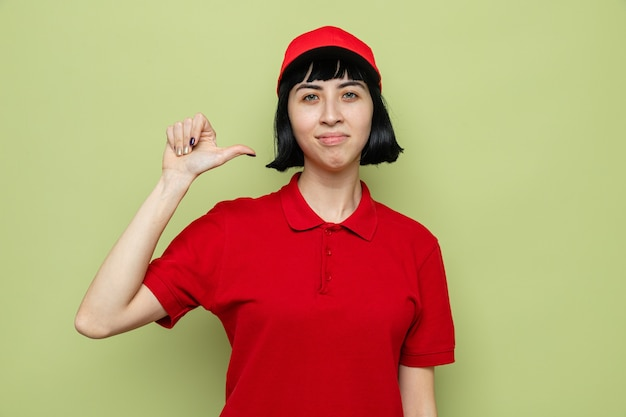 Pewna siebie młoda kaukaska dostarczająca kobieta wskazująca na siebie