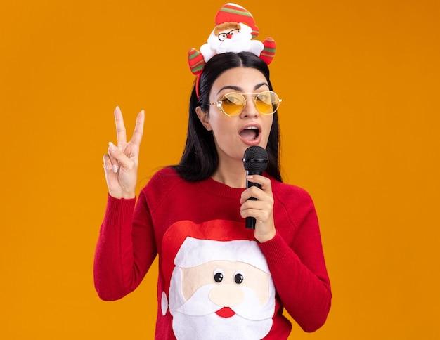 Pewna siebie młoda kaukaska dziewczyna ubrana w opaskę świętego mikołaja i sweter w okularach mówi do mikrofonu patrząc na kamerę robi znak pokoju na białym tle na pomarańczowym tle