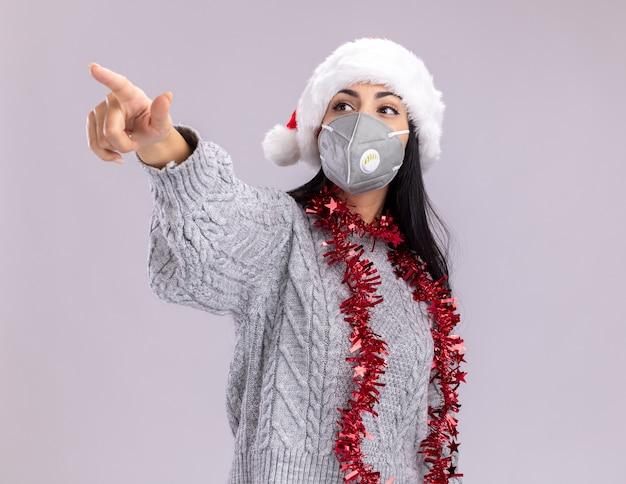 Pewna siebie młoda kaukaska dziewczyna ubrana w świąteczny kapelusz i świecącą girlandę na szyi z maską ochronną patrząc i wskazując na bok na białym tle na białym tle z miejsca na kopię
