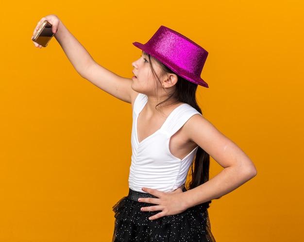 Pewna siebie młoda kaukaska dziewczyna w fioletowym kapeluszu imprezowym, patrząca na telefon, biorąca selfie na pomarańczowej ścianie z miejscem na kopię