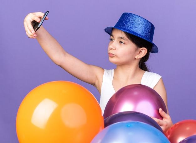 Pewna siebie młoda kaukaska dziewczyna w niebieskim kapeluszu imprezowym biorąca selfie na telefon stojący z balonami z helem odizolowanych na fioletowej ścianie z kopią przestrzeni