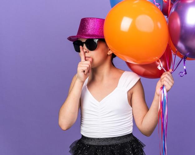 Pewna siebie młoda kaukaska dziewczyna w okularach przeciwsłonecznych z fioletowym kapeluszem imprezowym trzymająca balony z helem i wykonująca gest ciszy na fioletowej ścianie z kopią miejsca