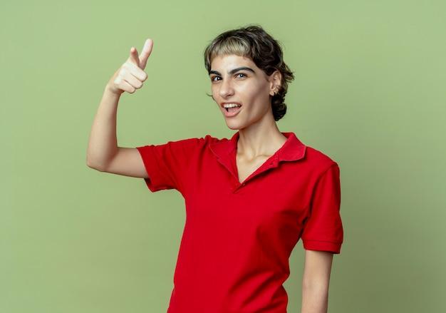 Pewna siebie młoda kaukaska dziewczyna z fryzurą pixie robi gest pistoletu ręką i wskazuje na aparat odizolowany na oliwkowym tle z miejsca na kopię