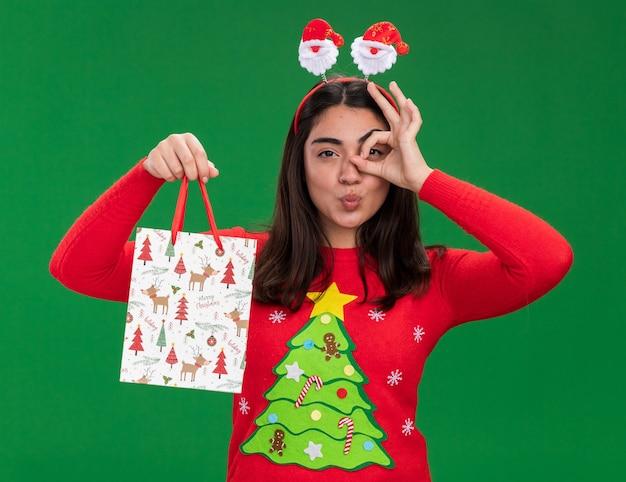 Pewna siebie młoda kaukaska dziewczyna z opaską mikołaja trzyma torbę z prezentami świątecznymi i patrzy na aparat przez palce odizolowane na zielonym tle z miejsca na kopię