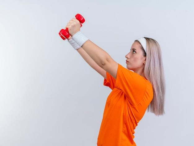 Pewna siebie młoda kaukaski dziewczyna sportowa z szelkami na sobie opaskę i opaski na nadgarstek