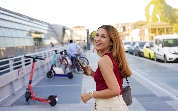 Pewna siebie młoda kobieta biznesu odwraca się, patrząc na kamerę i uśmiechając się za pomocą aplikacji na smartfona, która przygotowuje się do użycia skutera elektrycznego, aby wrócić do domu