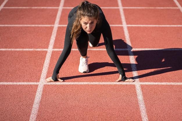 Pewna siebie młoda kobieta sprawny sprinter na stadionie gumowej bieżni lub bieżni przygotowuje się do rozpoczęcia biegu