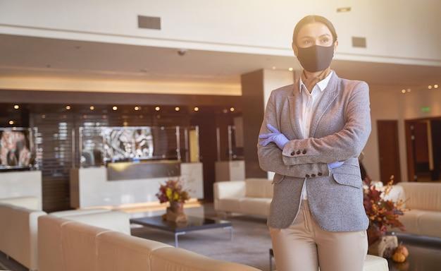 Pewna siebie młoda kobieta stojąca ze skrzyżowanymi rękami i odwracająca wzrok, będąc w holu centrum biznesowego
