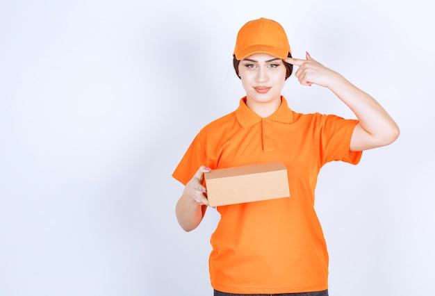 Pewna siebie młoda kobieta w niekształtnym, trzymająca palec przy głowie, trzymając pudełko