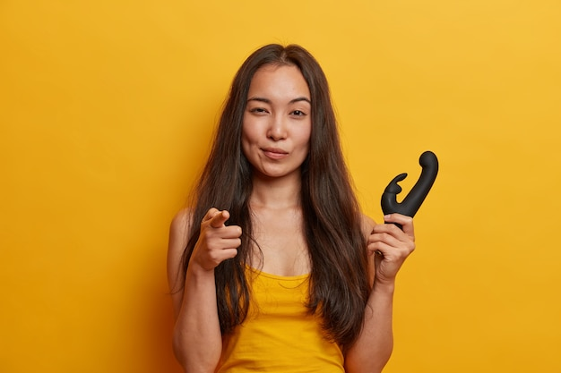 Pewna siebie młoda kobieta wskazuje palcem wskazującym, trzyma wibrator do stymulacji łechtaczki iskrzącymi wibracjami, ma osobiste dildo, odizolowane na żółtej ścianie. zabawka erotyczna dla kobiet.
