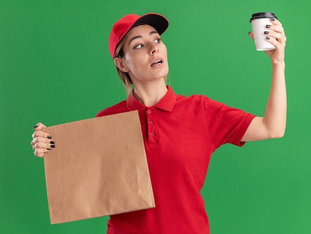 Pewna siebie młoda ładna dziewczyna dostawy w mundurze trzyma papierowy pakiet i patrzy na papierowy kubek na zielono