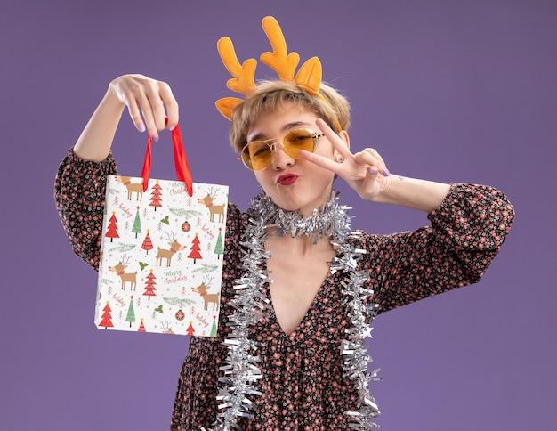Pewna siebie młoda ładna dziewczyna ubrana w opaskę z poroża renifera i świecącą girlandę na szyi w okularach trzyma torbę z prezentami świątecznymi, patrząc na kamery, robi znak pokoju na białym tle na fioletowym tle