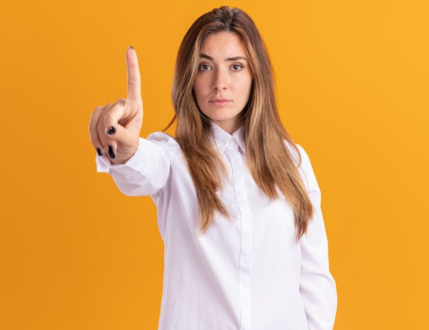 Pewna siebie młoda ładna kaukaska dziewczyna pokazuje palec wskazujący
