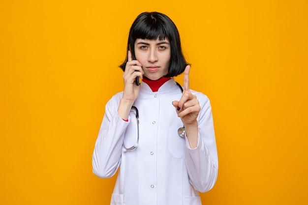 Pewna siebie młoda ładna kaukaska dziewczyna w mundurze lekarza ze stetoskopem rozmawia przez telefon i wskazuje w górę