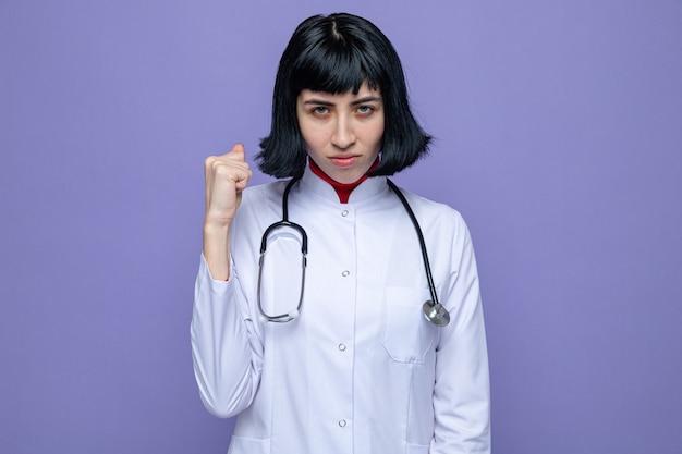 Pewna siebie młoda ładna kaukaska dziewczyna w mundurze lekarza ze stetoskopem trzymająca pięść i patrząca z przodu