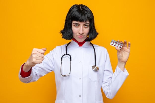 Pewna siebie młoda ładna kaukaska kobieta w mundurze lekarza ze stetoskopem trzymająca pigułki i trzymająca pięść