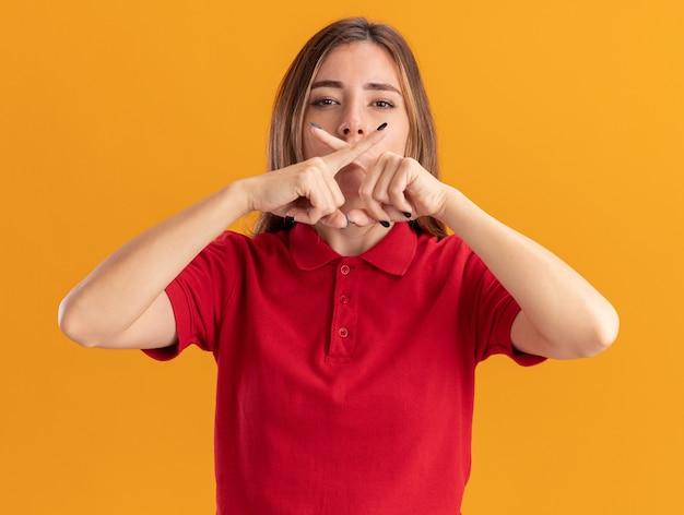 Pewna siebie młoda ładna kobieta krzyżuje palce wskazując na żaden znak na pomarańczowej ścianie