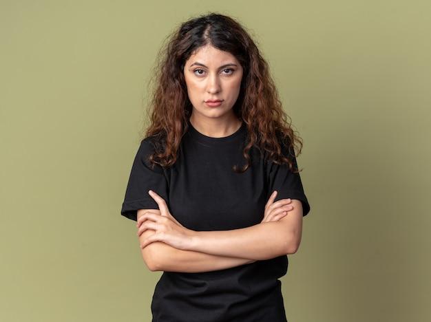 Pewna siebie młoda ładna kobieta stojąca z zamkniętą postawą, patrząc na przód odizolowana na oliwkowozielonej ścianie z miejscem na kopię