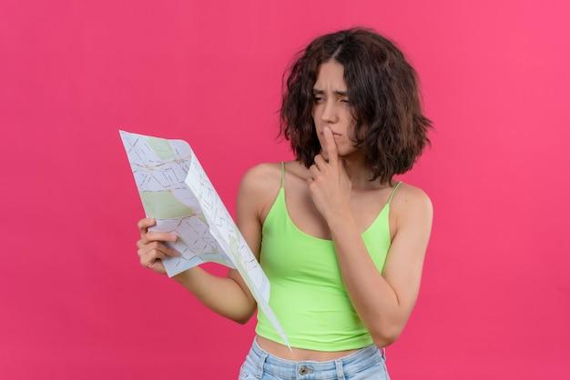Pewna siebie młoda ładna kobieta z krótkimi włosami w zielonej bluzce, trzymając palec wskazujący na ustach, patrząc na mapę
