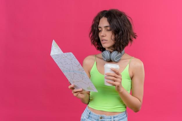 Pewna siebie młoda ładna kobieta z krótkimi włosami w zielonej bluzce w słuchawkach trzyma plastikową filiżankę kawy patrząc na mapę