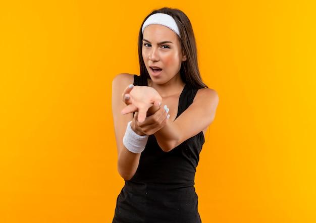 Pewna siebie młoda ładna sportowa dziewczyna nosząca opaskę na głowę i nadgarstek, wyciągając rękę i trzymającą rękę na białym tle na pomarańczowej ścianie