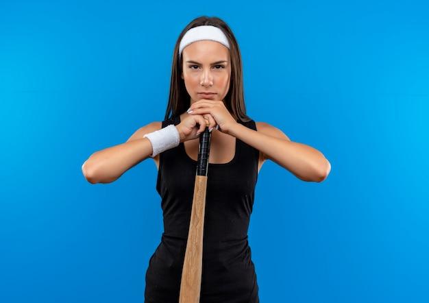 Pewna siebie młoda ładna sportowa dziewczyna nosząca opaskę na głowę i opaskę, trzymająca i kładąca ręce na kiju baseballowym odizolowana na niebieskiej ścianie