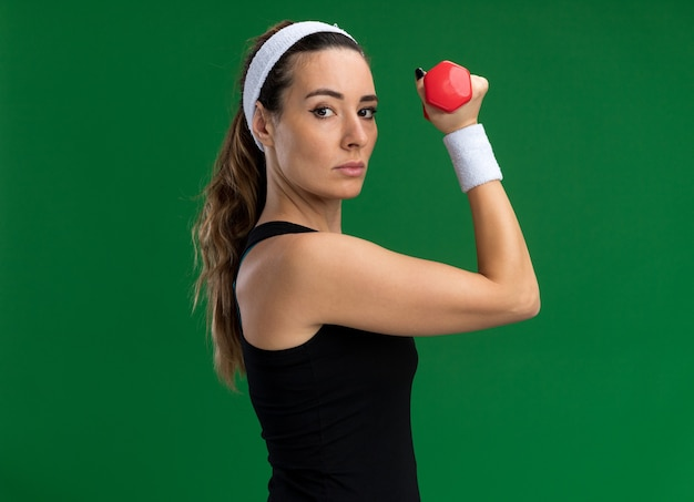 Pewna siebie młoda ładna sportowa kobieta nosząca opaskę i opaski stojąca w widoku z profilu trzymająca hantle