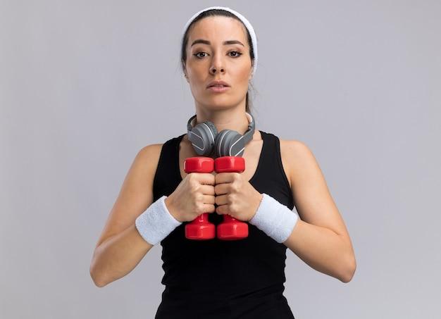 Pewna siebie młoda, ładna sportowa kobieta nosząca opaskę na głowę i nadgarstki trzymająca hantle wraz ze słuchawkami na szyi