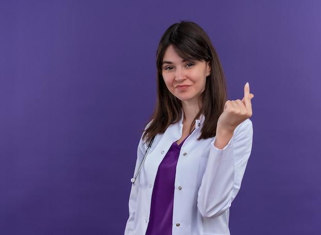 Pewna siebie młoda lekarka w szlafroku medycznym ze stetoskopem gestykuluje pieniądze ręką na odosobnionym fioletowym tle z miejsca na kopię
