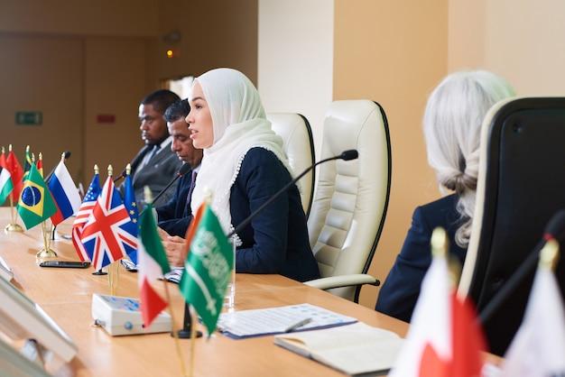 Pewna siebie młoda muzułmanka mówi do mikrofonu na konferencji lub forum politycznym wśród zagranicznych kolegów