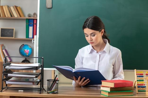 Pewna siebie młoda nauczycielka czytająca folder siedząca przy stole z narzędziami szkolnymi w klasie