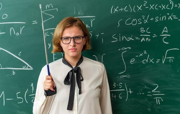 Pewna siebie młoda nauczycielka w okularach stojąca przed tablicą trzymająca kijek wskaźnika w klasie