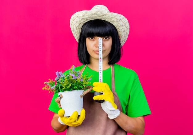 Pewna siebie młoda ogrodniczka w mundurze na sobie kapelusz ogrodniczy trzyma doniczkę i centymetr