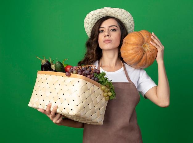 Pewna siebie młoda ogrodniczka w mundurze na sobie kapelusz ogrodniczy trzyma kosz warzyw i dyni na ramieniu na białym tle na zielonej ścianie z miejsca na kopię