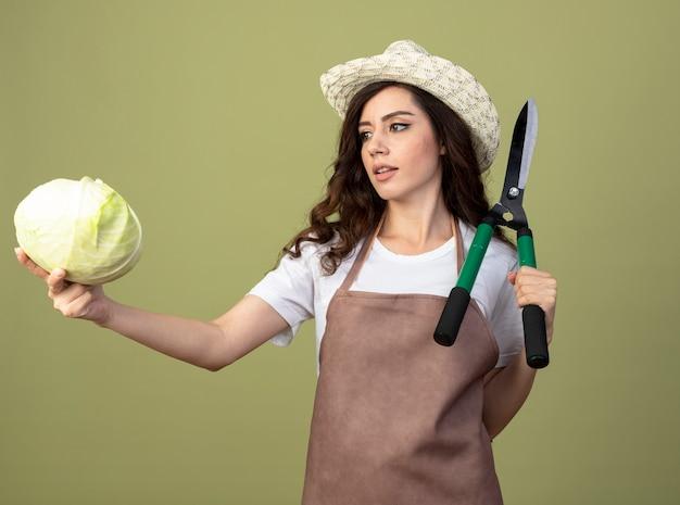 Pewna siebie młoda ogrodniczka w mundurze na sobie kapelusz ogrodniczy trzyma nożyce ogrodowe i patrzy na kapustę na białym tle na oliwkowej ścianie