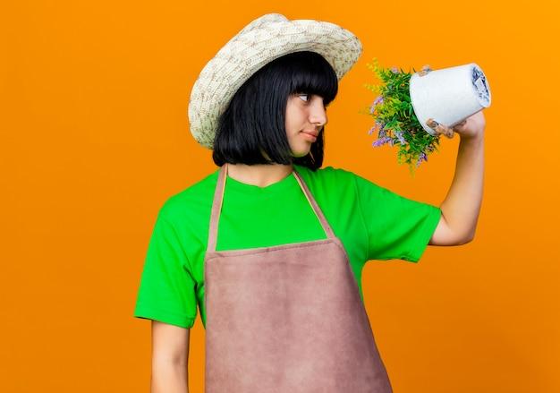 Pewna siebie młoda ogrodniczka w mundurze w kapeluszu ogrodniczym trzyma i patrzy na kwiaty w doniczce