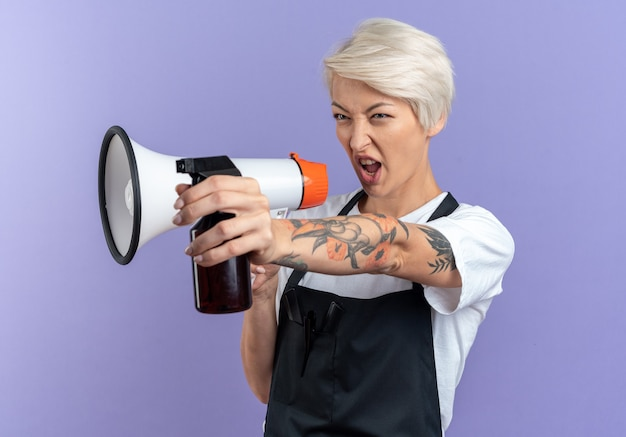 Pewna siebie młoda piękna fryzjerka w mundurze mówi przez głośnik trzymając butelkę z rozpylaczem z boku na białym tle na niebieskiej ścianie