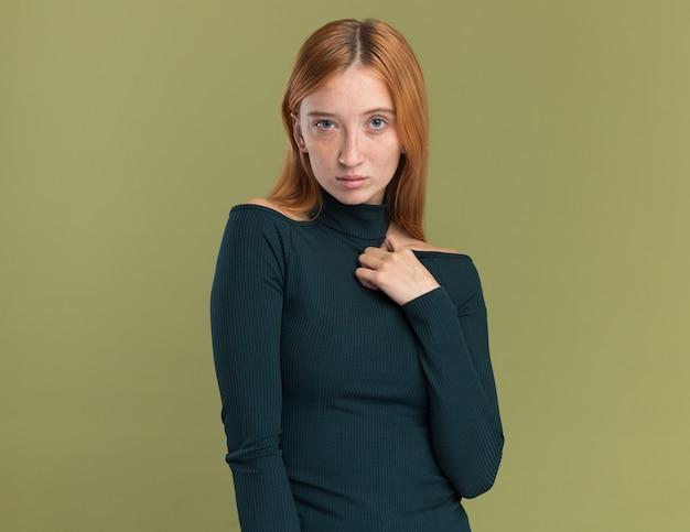 Pewna siebie młoda rudowłosa dziewczyna z piegami kładzie rękę na klatce piersiowej i patrzy na kamerę