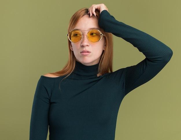Pewna siebie młoda rudowłosa dziewczyna z piegami w okularach przeciwsłonecznych kładzie rękę na głowie i patrzy na bok