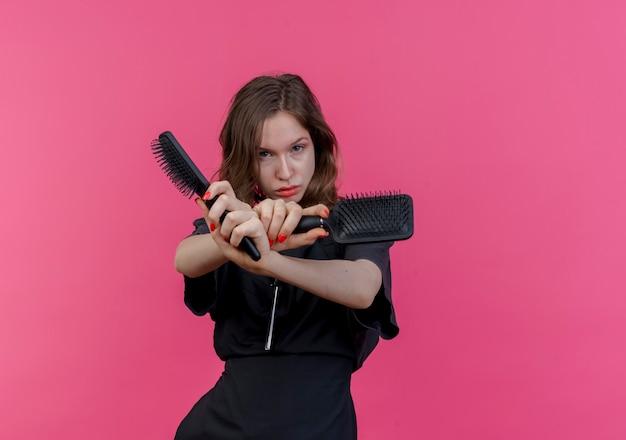 Pewna siebie młoda słowiańska fryzjerka nosząca mundur wyciągając ręce trzymające grzebienie i nie wykonująca żadnego gestu