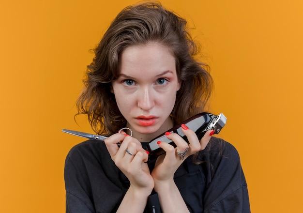 Pewna siebie młoda słowiańska fryzjerka w mundurze trzymająca nożyczki i maszynki do strzyżenia włosów