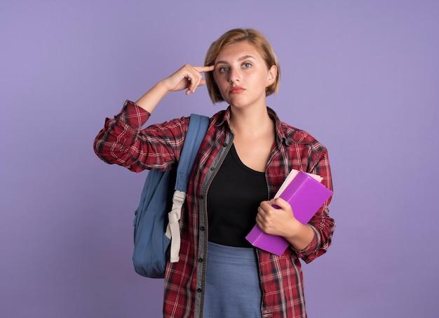 Pewna siebie młoda słowiańska studentka nosząca plecak kładzie palec na świątyni, trzyma książkę i notatnik