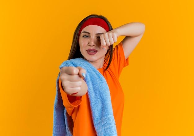 Pewna siebie młoda sportowa kobieta nosząca opaskę i opaski na rękę z ręcznikiem i na ramieniu, wykonująca gest bokserski na pomarańczowej ścianie z miejscem na kopię