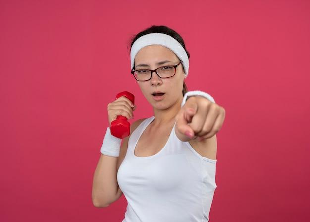 Pewna siebie młoda sportowa kobieta w okularach optycznych na sobie opaskę i opaski na nadgarstek trzyma hantle i wskazuje z przodu na białym tle na różowej ścianie